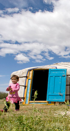 Child Standing In Front of A Yurt