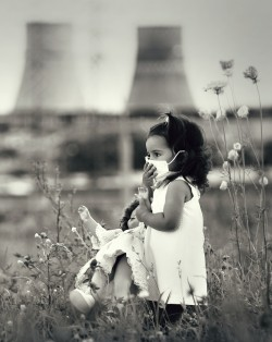child in a respiratory mask with a doll in her hands walking against power station polluting air coal