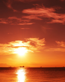 dramatic manila bay sunset with boats and ships in horizon.